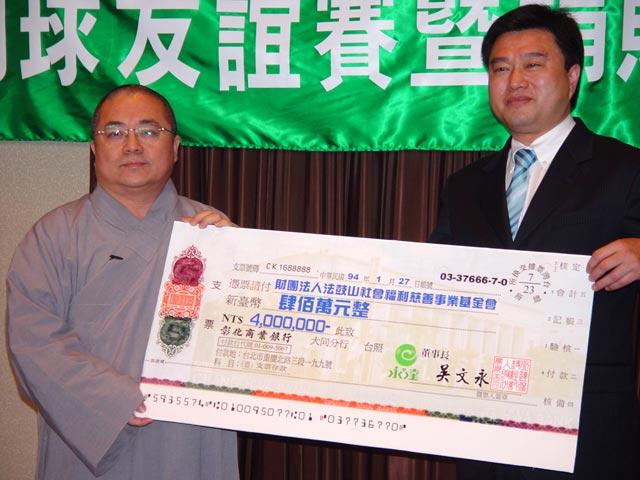 捐南亞賑災款項董事長與法師拿著支票看板合影。