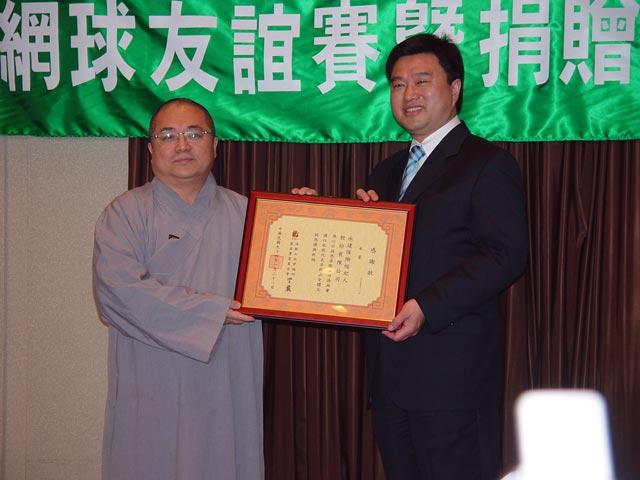 捐南亞賑災款項董事長與法師拿著感謝狀合影。